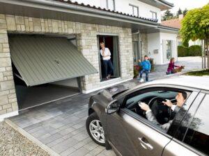 Ein Mann öffnet bequem mit dem Handsender das Garagentor