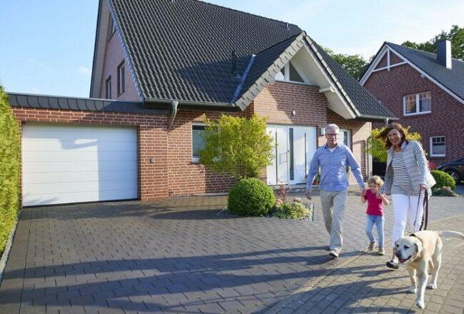 Familie spaziert vor dem Eigenheim